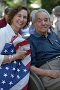 A young woman sitting, smiling and holding an American flag next to an elderly gentleman - also seated and smiling