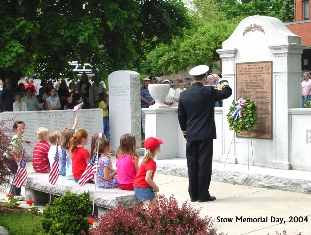 Large marble stone with memorial plaque surrounded by los marble walls. Children are sitting between the 2 walls and in front of memorial stone.  Uniformed officer is facing stone and saluting